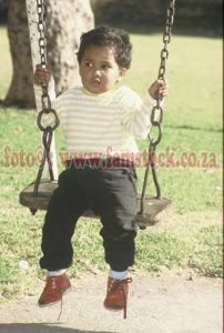 k6128- very non-smiling boy toddler on swing in bright sunlight