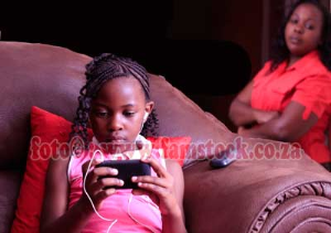mother watching preteen daughter busy on mobile device | Photos and Images | Children