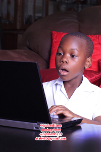 black pre-teen boy shocked at what he sees on laptop screen