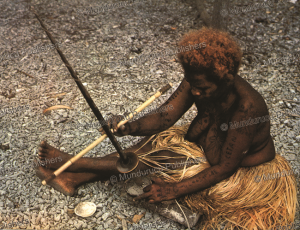 tattooed woman makes a fire, solomon islands